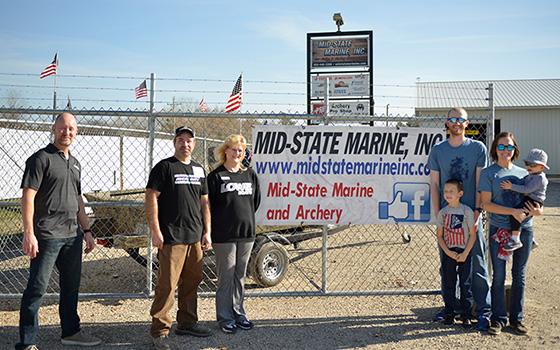 Greg Falkner, General Manger of Lowe, Tom D'Amico and Julie Ruedinger of Mid-State Marine, and Josh's family at Mid-State Marine's Fremont dealership.