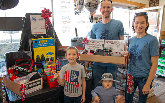 Josh and family posing with fishing and gear awarded with his boat in the Mid-State Showroom. Special thanks to Mercury Marine, Favorite fishing rods and reels, and Kellogg Marine Supply.